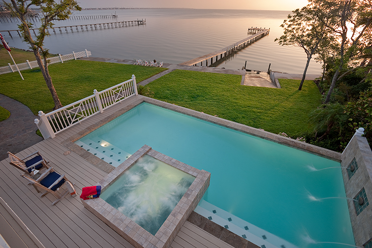 Architectural photograph of view from guest bedroom balcony overlooking pool, hot tub and pier into bay
