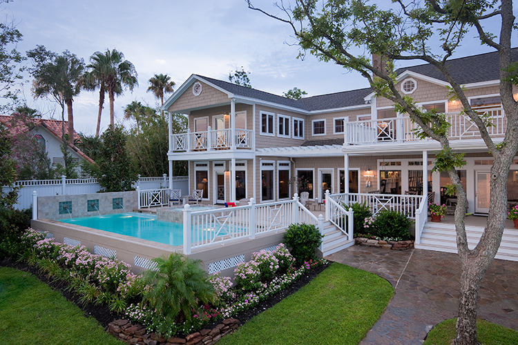 Exterior photographof bay home with pool and deck