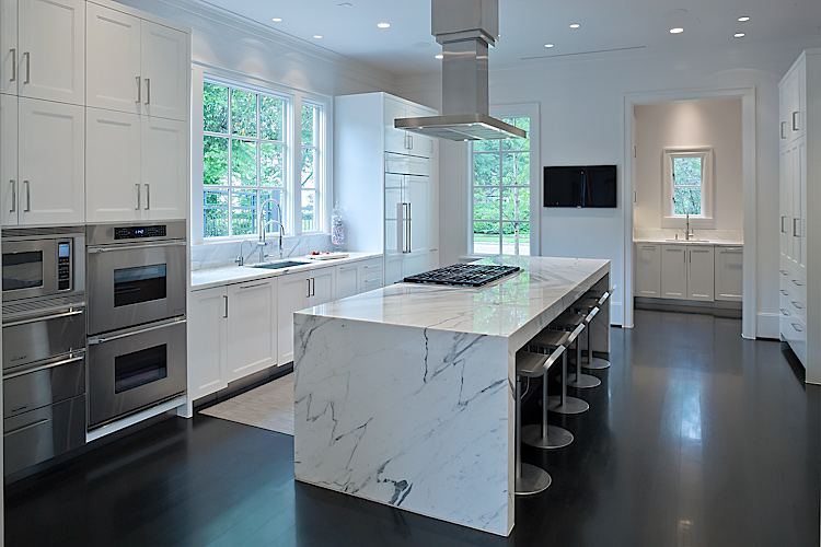 architectural photograph of modern kitchen with marble island and stainless steal appliances